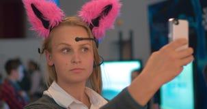 Mulher com as orelhas neuro que fazem o selfie video estoque