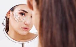 Mulher com as setas de levantamento na cara que olha no espelho Fotografia de Stock