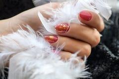 Mulher com as unhas vermelhas manicured bonitas que cruzam graciosamente suas mãos para indicá-las ao visor em um branco Imagens de Stock