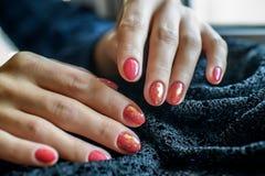 Mulher com as unhas vermelhas manicured bonitas que cruzam graciosamente suas mãos para indicá-las ao visor em um cinza Foto de Stock Royalty Free