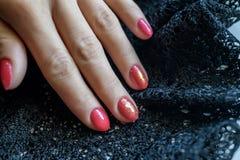 Mulher com as unhas vermelhas manicured bonitas que cruzam graciosamente suas mãos para indicá-las ao visor em um cinza Foto de Stock