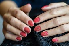 Mulher com as unhas vermelhas manicured bonitas que cruzam graciosamente suas mãos para indicá-las ao visor em um cinza Imagem de Stock