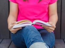 Mulher com assento do livro fotos de stock royalty free