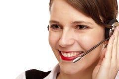 A mulher com auriculares ri feliz e faz um atendimento Imagens de Stock Royalty Free