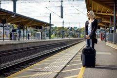 Mulher com a bagagem que espera na plataforma da estação de estrada de ferro fotos de stock royalty free