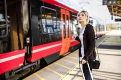 Mulher com a bagagem que está no estação de caminhos-de-ferro imagens de stock royalty free