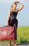 Mulher com a bagagem que olha na distância Fotos de Stock Royalty Free