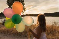 Mulher com balões coloridos que olha o por do sol fotografia de stock royalty free