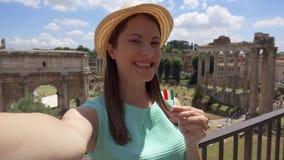 A mulher com a bandeira italiana perto do fórum Romanum faz o selfie O turista fêmea toma a foto contra o fórum romano video estoque
