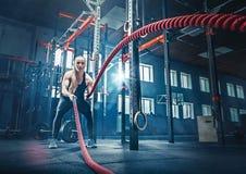 A mulher com batalha da corda da batalha ropes o exercício no gym da aptidão fotografia de stock