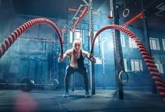 A mulher com batalha da corda da batalha ropes o exercício no gym da aptidão imagem de stock