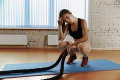 A mulher com batalha ropes o exercício no gym da aptidão foto de stock
