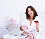 Mulher com bebê, cartão de crédito e portátil em casa imagens de stock royalty free