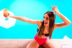 Mulher com bebida do cocktail na borda da piscina Imagens de Stock