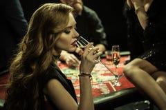 Mulher com a bebida que joga o pôquer no casino imagens de stock