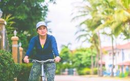 Mulher com a bicicleta do passeio do terno de gym para o exercício no jardim da vila dentro Imagem de Stock
