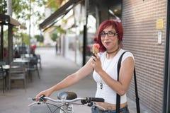 A mulher com a bicicleta do passeio na cidade e come o gelado na soma Foto de Stock