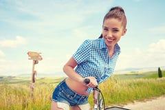Mulher com bicicleta do vintage em uma estrada secundária Fotos de Stock Royalty Free