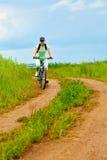 Mulher com a bicicleta no campo verde foto de stock royalty free