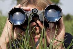 A mulher com binóculos está descobrindo fotografia de stock