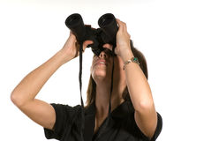 A mulher com binóculos olha acima Foto de Stock