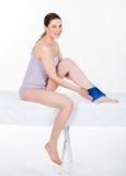 Mulher com bloco de gelo no tornozelo foto de stock