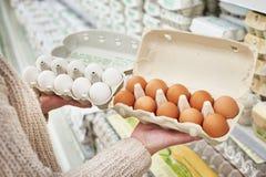 Mulher com blocos dos ovos brancos e marrons na loja Imagens de Stock