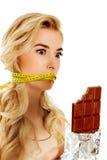 Mulher com a boca amarrada que guarda a barra de chocolate Foto de Stock