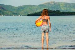 Mulher com a bola de praia na praia Imagens de Stock Royalty Free