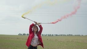 Mulher com a bomba de fumo colorido que relaxa na natureza vídeos de arquivo