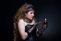 Mulher com bordos, ouropel e o wineglass vermelhos sobre Fotografia de Stock