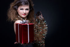 Mulher com bordos, ouropel e presente vermelhos no bl Fotografia de Stock Royalty Free