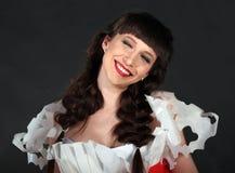 A mulher com bordos vermelhos que sorri e e que fecha-se eyes Foto de Stock