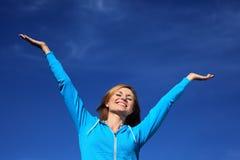 A mulher com braços outstretched de encontro ao céu azul Foto de Stock Royalty Free