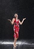 Mulher com braços que aprecia para fora a chuva foto de stock