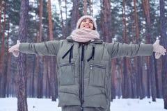 Mulher com braços espalhados que aprecia a beleza da floresta do inverno Imagens de Stock