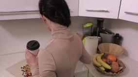 Mulher com a câmera profissional que relaxa e e café bebendo na cozinha vídeos de arquivo