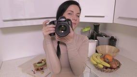 A mulher com câmera profissional toma imagens na cozinha filme