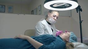 A mulher com cabelo branco longo aplica a composição permanente da sobrancelha video estoque