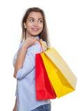 Mulher com cabelo escuro longo e os sacos de compras que olham lateralmente Fotografia de Stock