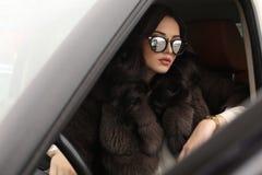 Mulher com cabelo escuro na roupa elegante e no casaco de pele luxuoso fotos de stock royalty free