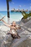 A mulher com cabelo longo louro no vestido longo encontra-se em uma rede no fundo do mar Foto de Stock Royalty Free