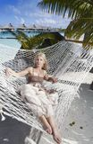 A mulher com cabelo longo louro no vestido longo encontra-se em uma rede no fundo do mar Fotos de Stock Royalty Free