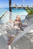A mulher com cabelo longo louro no vestido longo encontra-se em uma rede no fundo do mar Imagens de Stock Royalty Free