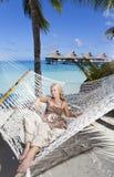 A mulher com cabelo longo louro no vestido longo encontra-se em uma rede no fundo do mar Foto de Stock
