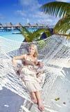 A mulher com cabelo longo louro no vestido longo encontra-se em uma rede no fundo do mar Imagens de Stock