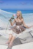 A mulher com cabelo longo louro no vestido longo com uma rosa encontra-se em uma rede no fundo do mar Foto de Stock Royalty Free