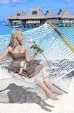 A mulher com cabelo longo louro no vestido longo com uma rosa encontra-se em uma rede no fundo do mar Imagens de Stock