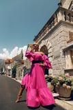 Mulher com cabelo louro no vestido cor-de-rosa luxuoso, tendo o verão VAC foto de stock