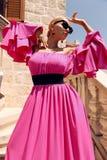 Mulher com cabelo louro no vestido cor-de-rosa luxuoso, tendo o verão VAC imagem de stock